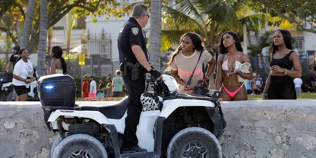 FILE - In this March 14, 2020, file photo, Amaya Herron, a student at the University of Memphis on spring break, left, talks with a Miami Beach police officer in Miami Beach, Fla. Colleges around the U.S. are scaling back spring break or canceling it entirely to discourage beachfront partying that could raise infection rates back on campus. (AP Photo/Lynne Sladky, File)