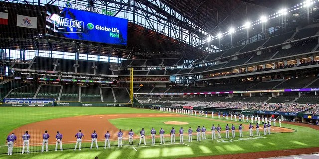 FILE - The Texas Rangers and Colorado Rockies line the foul lines of Globe Life Field before an opening day baseball game in Arlingtn, Texas, in this Friday, July 24, 2020, file photo. (AP Photo/Jeffrey McWhorter, File)