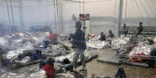 This March 20, 2021, photo provided by the Office of Rep. Henry Cuellar, D-Texas, shows detainees in a Customs and Border Protection (CBP) temporary overflow facility in Donna, Texas. (Photo courtesy of the Office of Rep. Henry Cuellar via AP)
