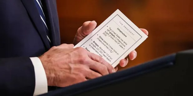 President Biden holds up one of the 'cheat sheets' that he was seen using during Thursday's press conference at the White House.  (Reuters)