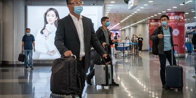 Travelers wearing protective masks push their luggage through Beijing Capital International Airport in Beijing, China, on Wednesday, Sept. 30, 2020. (Photographer: Yan Cong/Bloomberg via Getty Images)