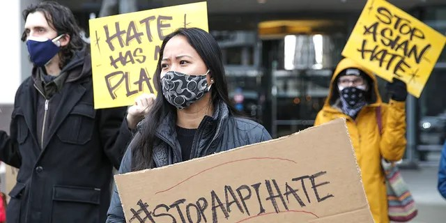 "Trish Villanueva (C) of Seattle holds a sign with the hashtag ""stop AAPI hate"" during the We Are Not Silent rally organized by the Asian American Pacific Islander (AAPI) Coalition Against Hate and Bias in Bellevue, Washington on March 18, 2021. (Photo by Jason Redmond / AFP) (Photo by JASON REDMOND/AFP via Getty Images)"