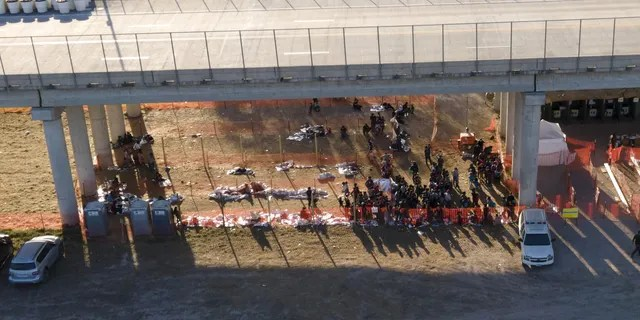 In this photo taken by a drone, migrants are seen in custody at a U.S. Customs and Border Protection processing area under the Anzalduas International Bridge, Thursday, March 18, 2021, in Mission, Texas. . (AP Photo/Julio Cortez)