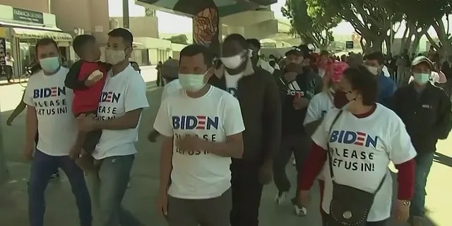 Migrants at the Southern border wear shirts asking President Biden to let them into the U.S.