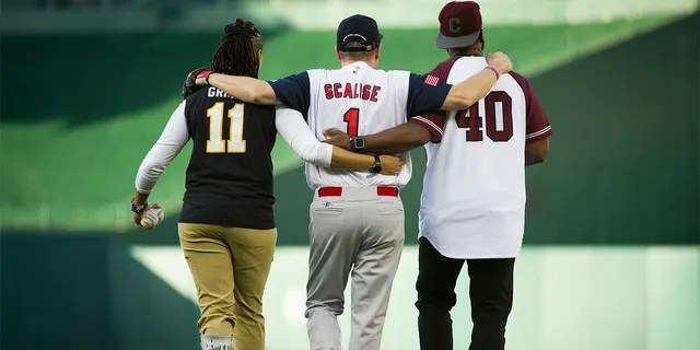 Capitol Police Special Agents Crystal Griner, left, and David Bailey, right, assist U.S. Rep. Steve Scalise to his position at second base at the start of the 57th Congressional Baseball Game at National's Park in Washington, Thursday, June 14, 2018.