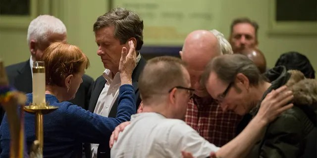 Toronto Mayor John Tory (left) took part in an anointing ceremony at Metropolitan Community Church, which held a candlelight prayer vigil for the victims of serial killer Bruce McArthur.  February 4, 2018.