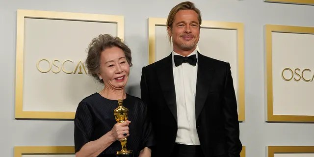 """Brad Pitt, right, poses with Yuh-Jung Youn, winner of the award for best actress in a supporting role for """"Minari,"""" in the press room at the Oscars on Sunday, April 25, 2021, at Union Station in Los Angeles."""