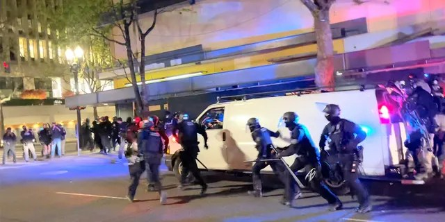 Riot police ran towards protesters in Portland, Oregon, U.S. on April 16, 2021, in this video still.  Grace Morgan via REUTERS THIS IMAGE HAS BEEN PROVIDED BY A THIRD PARTY.  MANDATORY CREDIT.  NO RESALE.  NO ARCHIVES.
