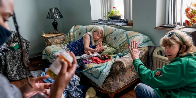March 17, 2021: Sue Howland, right, and Larrecsa Cox, left, members of the Quick Response Team whose mission is to save every citizen who survives an overdose from the next one, help Betty Thompson, 65, who struggles with alcohol addiction, count her medications at her apartment in Huntington, W.Va.