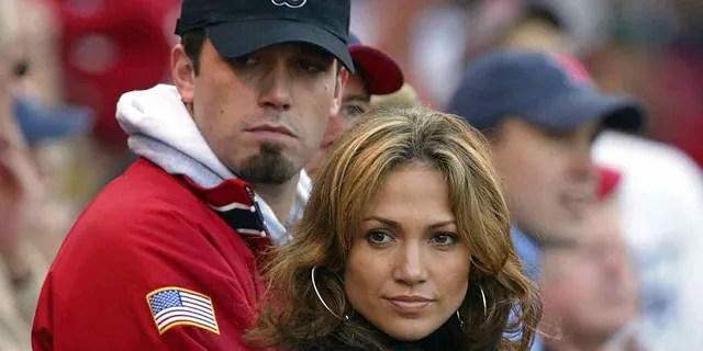 Actress-singer Jennifer Lopez and boyfriend, actor Ben Affleck, watch the New York Yankees take on the Boston Red Sox during Game 3 of the 2003 American League Championship Series on October 11, 2003, at Fenway Park in Boston, Massachusettes.