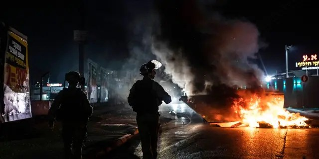 Israeli police patrol during clashes between Arabs, police and Jews, in the mixed town of Lod, central Israel, Wednesday, May 12, 2021.
