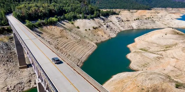 A car crosses Enterprise Bridge over Lake Oroville's dry banks Sunday, May 23, 2021, in Oroville, California. At the time of this photo, the reservoir was at 39 percent of capacity and 46 percent of its historical average. (Associated Press)