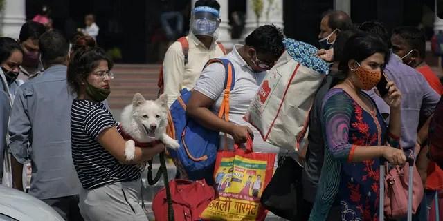 June 7, 2021: Passengers walk outside the New Delhi railway station in New Delhi.