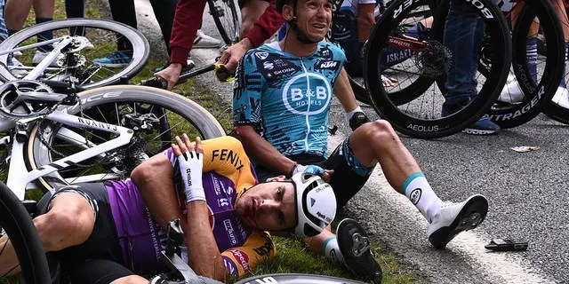 Italy's Kristian Sbaragli, left, and France's Bryan Coquard, right, lie on the ground after crashing during the first stage of the Tour de France. (Anne-Christine Poujoulat, Pool Photo via AP)