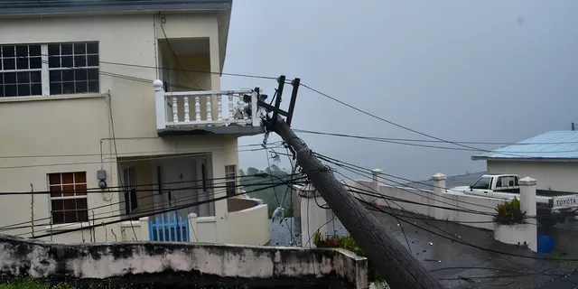 An electrical pole felled by Hurricane Elsa leans on the edge of a residential balcony, in Cedars, St. Vincent, Friday, July 2, 2021. (Associated Press)