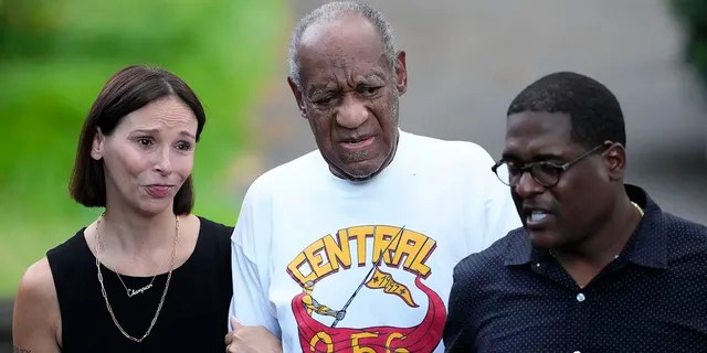 Comedian Bill Cosby, center, and spokesperson Andrew Wyatt, right, approach members of the media gathered outside Cosby's home in Elkins Park, Pa., Wednesday, June 30, 2021, after Pennsylvania's highest court overturned his sex assault conviction. (AP Photo/Matt Rourke)