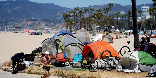 A jogger walks past a homeless encampment in the Venice Beach section of Los Angeles, June 8, 2021. (Associated Press)