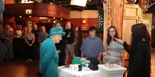 Britain's Queen Elizabeth II meets actors and members of the production team during a visit to the set of the long running television series Coronation Street, in Manchester, England, Thursday July 8, 2021.