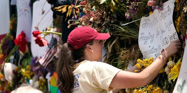 Molly MacDonald, with Mercy Chefs, hangs a sign on behalf of Princeton Church at a makeshift memorial remembering the victims of the nearby collapsed Champlain Towers South building, Wednesday, July 14, 2021, in Surfside, Fla. Mercy Chefs has set up a mobile kitchen to feed search and rescue teams working at the site three meals a day. (AP Photo/Lynne Sladky)