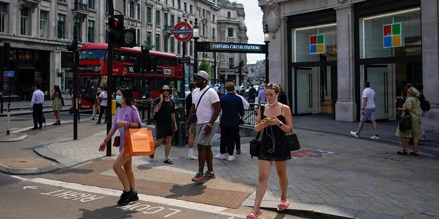People walk in Oxford Circus, in London, Monday, July 19, 2021. As of Monday, face masks are no longer legally required in England, and with social distancing rules shelved, there are no limits on the number of people attending theater performances or big events. (AP Photo/Alberto Pezzali)
