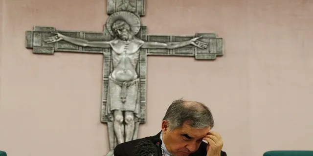 FILE - In this Friday, Sept. 25, 2020 file photo, Cardinal Angelo Becciu looks down as he meets the media during a press conference in Rome. (AP Photo/Gregorio Borgia, File)
