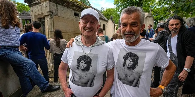 Fred Verheijden, left, and Hans van Schie of the Netherlands wear shirts with a photo of late rock singer Jim Morrison at the Pere-Lachaise cemetery in Paris, Saturday, July 3, 2021. (Associated Press)