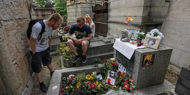 Joachim Tittmar from Germany, left, Walter Homburg of the Netherlands, center, and his girlfriend Kate Schirm gather at the tomb of rock singer Jim Morrison at the Pere-Lachaise cemetery in Paris, Saturday, July 3, 2021. (Associated Press)
