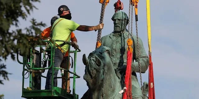 Workers remove a statue of Confederate General Robert E. Lee, after years of a legal battle over the contentious monument, in Charlottesville, Virginia, the U.S, July 10, 2021. REUTERS/Evelyn Hockstein