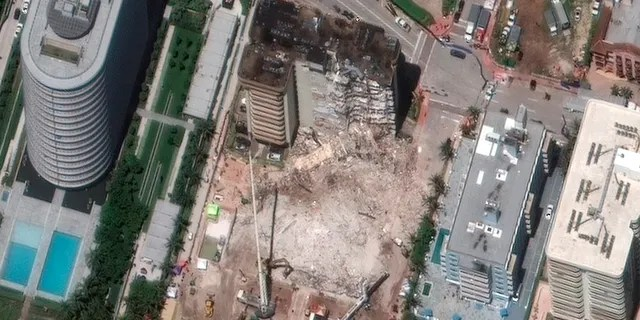 In this satellite image provided by Maxar Technologies heavy-lift cranes are used to aid in the search and recovery operation at the partially collapsed Champlain Towers South condo building on Saturday, July 3, 2021, in Surfside, Fla. (Maxar Technologies via AP)