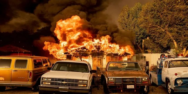 Flames consume a home as the Sugar Fire, part of the Beckwourth Complex Fire, tears through Doyle, Calif., on Saturday, July 10, 2021. Pushed by heavy winds amid a heat wave, the fire came out of the hills and destroyed multiple residences in central Doyle. (AP Photo/Noah Berger)