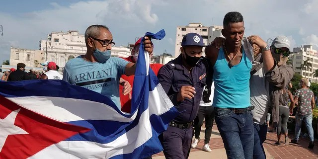 Police detain a person during protests against and in support of the government, amidst the coronavirus disease (COVID-19) outbreak, in Havana, Cuba July 11, 2021.