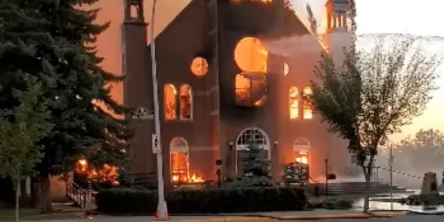Flames engulf a Catholic church as firefighters work to extinguish the fire at St. Jean Baptiste Parish in Morinville, Alberta, Canada