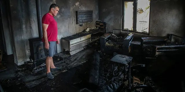 A man stands inside his burnt out house in Cokertme village, near Bodrum, Mugla, Turkey, Tuesday, Aug. 3, 2021.
