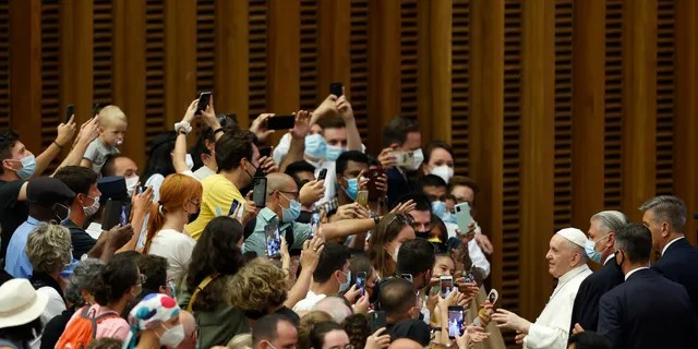 Pope Francis greets the faithful at the end of his weekly general audience in the Paul VI hall at the Vatican, Wednesday, Aug. 4, 2021. Pope Francis on Wednesday resumed his routine of weekly audiences with the general public a month after he underwent bowel surgery, expressing his desire to visit someday Lebanon, as he recalled the first anniversary of the devastating Beirut port explosion. (AP Photo/Riccardo De Luca)