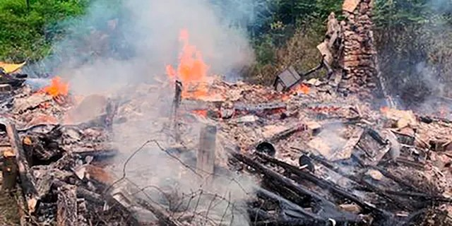 In this photo provided by the Canterbury (New Hampshire) Fire Department, smoke rises Wednesday, Aug. 4, 2021, from the burnt remains of a cabin in Canterbury, N.H., inhabited by 81-year-old David Lidstone, who for 27 years has lived in the woods of New Hampshire along the Merrimack River in the once small, solar-paneled cabin.