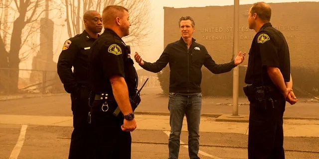 California Gov. Gavin Newsom speaks with law enforcement personnel while surveying damage to Greenville, which suffered extensive structure loss during the Dixie Fire, on Saturday, Aug. 7, 2021, in Plumas County, California. (Associated Press)