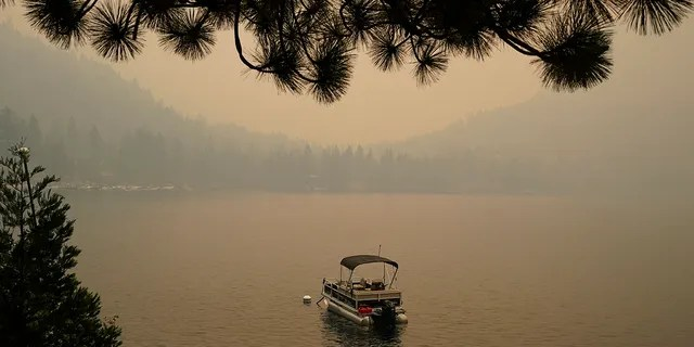 Smoke from the Caldor Fire, shrouds Fallen Leaf Lake near South Lake Tahoe, Calif., on Tuesday. The massive wildfire that is over a week old has scorched more than 190 square miles and destroyed hundreds of homes since Aug. 14.