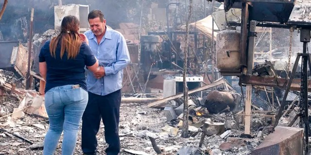 Homeowner Jose Lamas, right, and his daughter Astrid Covarrubias survey the charred debris left in his burned-out home from the South Fire in Lytle Creek, San Bernardino County, north of Rialto, Calif., Wednesday, Aug. 25, 2021.
