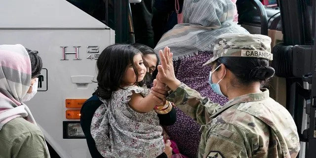 Army Pfc. Kimberly Hernandez gives a high-five to a girl evacuated from Kabul, Afghanistan, before boarding a bus after they arrived at Washington Dulles International Airport, in Chantilly, Va., on Monday.