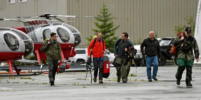Ketchikan Volunteer Rescue Squad personnel land and disembark from a Hughes 369D helicopter on Thursday, Aug. 5, 2021, at Temsco Helicopters in Ketchikan, Alaska. (Associated Press)