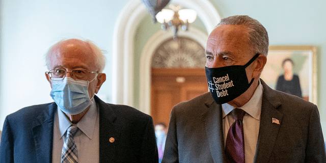 Sen. Bernie Sanders, I-Vt., left, and Senate Majority Leader Chuck Schumer of N.Y., right, walk out of a budget resolution meeting at the Capitol in Washington, Monday, Aug. 9, 2021. Schumer said Wednesday that he's confident spending and inflation concerns by moderate senators won't derail the reconciliation package spearheaded by Sanders. (AP Photo/Andrew Harnik)