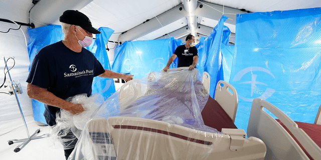 Samaritan's Purse staff set up a portable bed in one of four wards that are part of the 32-bed Samaritan's Purse Emergency Field Hospital set up in one of the University of Mississippi Medical Center's parking garages, Tuesday, Aug. 17, 2021, in Jackson, Miss. (AP Photo/Rogelio V. Solis)