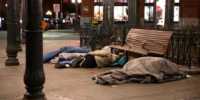 People sleep outside on a sidewalk on April 6, 2020 in Seattle. (Photo by Karen Ducey/Getty Images)