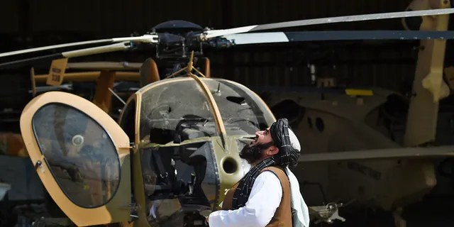 A Taliban member looks up near a damaged helicopter at the airport in Kabul on Tuesday.