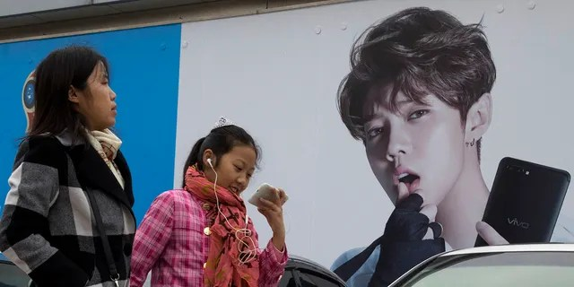 In this 2017, file photo, Chinese women walk past advertisement featuring teen idol Lu Han, also known as China's Justin Bieber in Beijing.