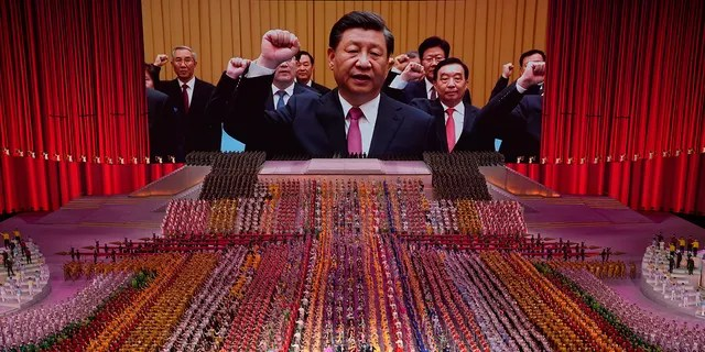 In this June 28, 2021, file photo, Chinese President Xi Jinping is seen leading other top officials pledging their vows to the party on screen during a gala show ahead of the 100th anniversary of the founding of the Chinese Communist Party in Beijing.