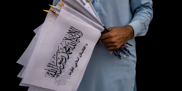 A street vendor selling Taliban flags waits for customers outside the American embassy compound in Kabul, Afghanistan, Saturday, Sept. 11, 2021.