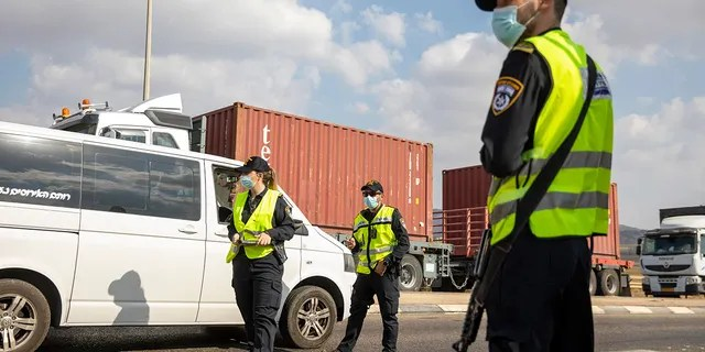 Israeli police check cars with Palestinian laborers as they search for two Palestinians who broke out of a maximum-security prison last week, on a road leading to the West Bank town of Jenin, near Gan Ner Israel, Sunday, Sept. 12, 2021. (AP Photo/Ariel Schalit)