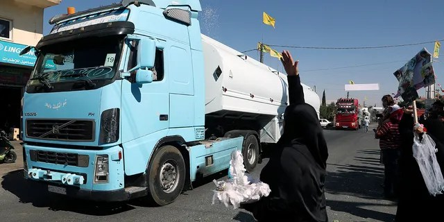 A Hezbollah supporter throws rice over a convoy of tanker trucks carrying Iranian diesel crossed the border from Syria into Lebanon, arrive at the eastern town of el-Ain, Lebanon, Thursday, Sept. 16, 2021.
