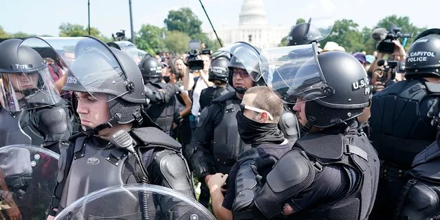 Police surround a man with glasses during a rally near the US Capitol in Washington, Saturday, September 18, 2021.  The rally was planned by aides of former President Donald Trump and aimed at supporting so-called